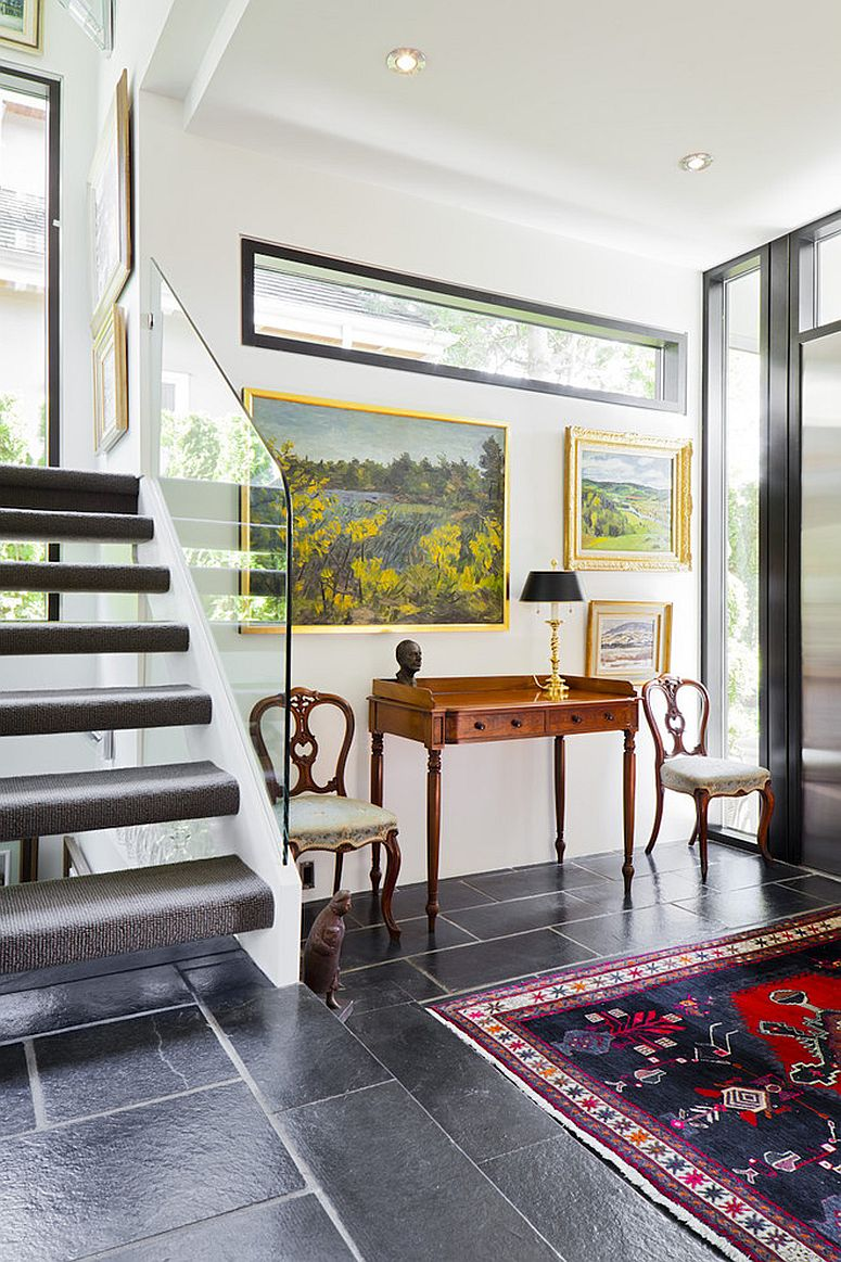 Modern entry with lovely paintings creates a stylish gallery wall [Design: Natural Balance Home Builders]