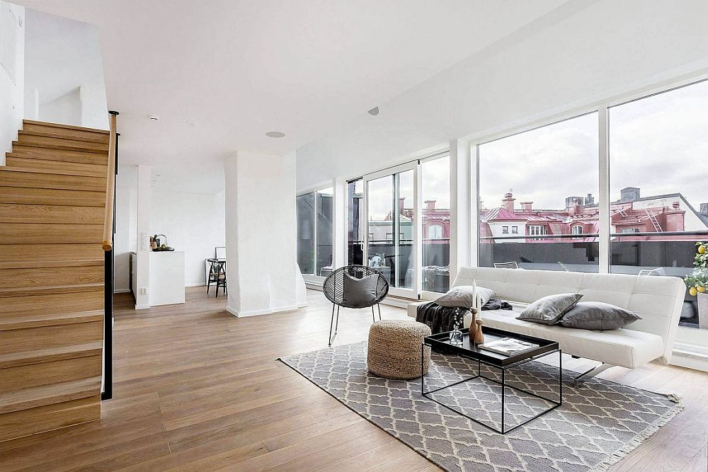 Open living area of the Scandinavian style apartment connected to the lovely balcony outside