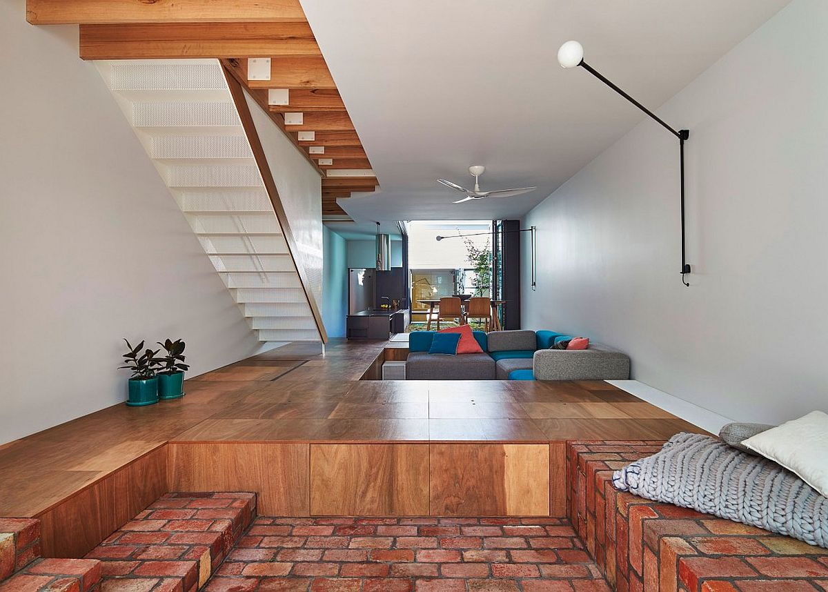 Perforated metal staircase design and sunken storage zone and seating in the living room