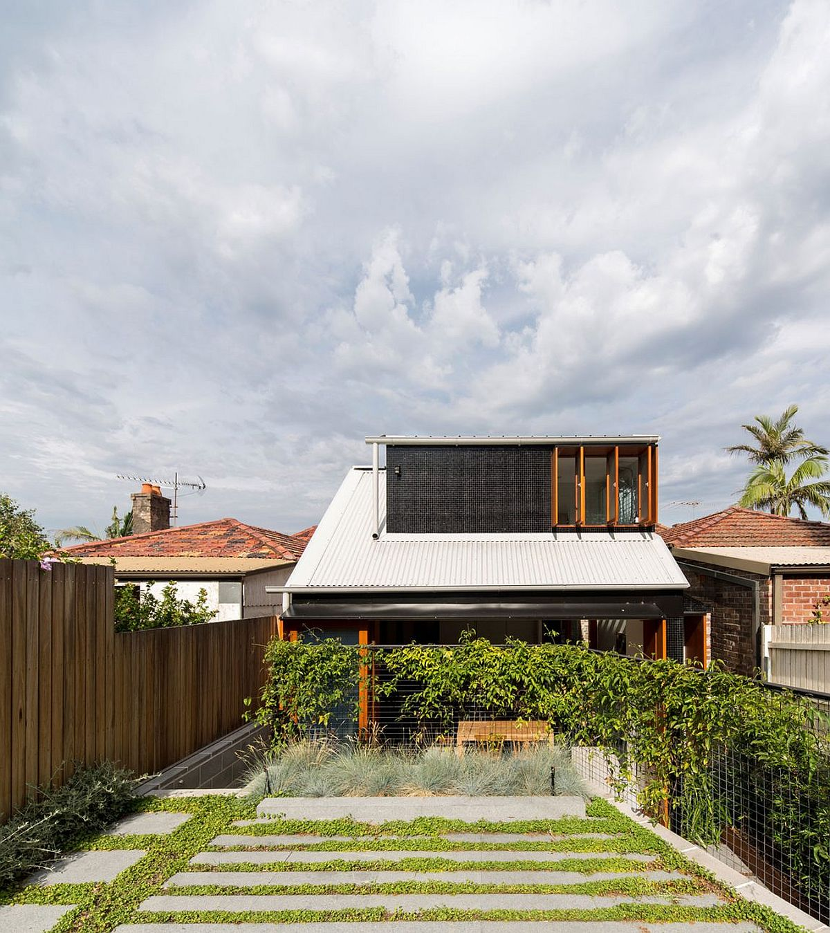 Rear garden of Downsize Upsize House in North Shore Sydney Budget Family Home in Sydney Uses Reclaimed Bricks, Concrete and Tile