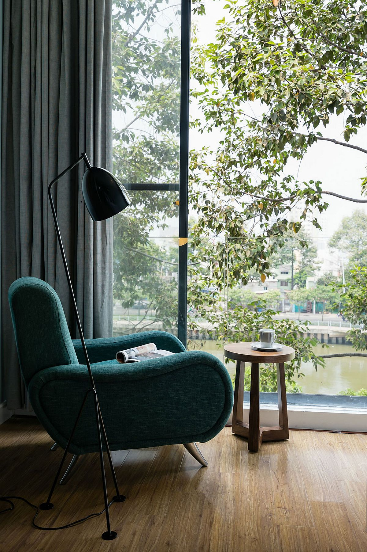 Simple reading nook with floor lamp that offers a view of the canal and green preserve around it