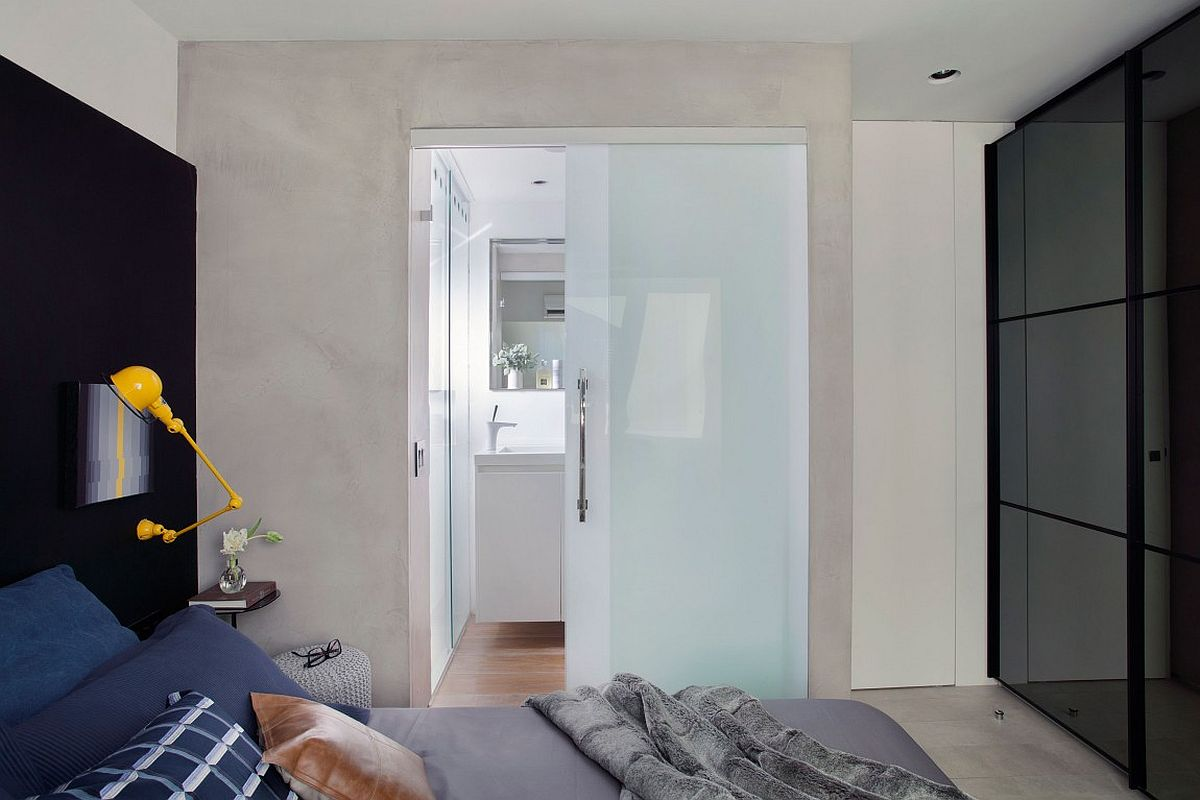 Sliding translucent glass door separates the bathroom from the bedroom