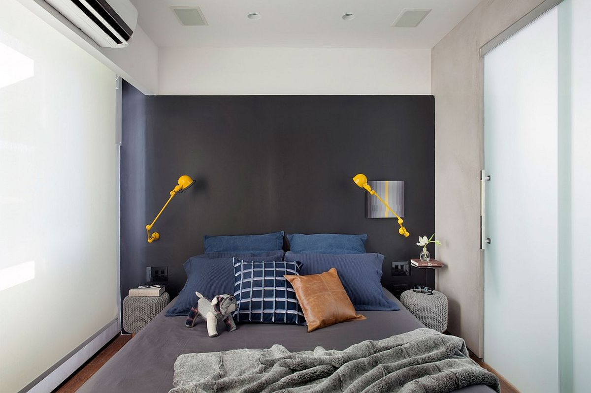 Small contemporary bedroom with gray accent wall and bright yellow sconce lighting