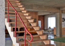 Striking wooden staircase with unqiue, colorful railing connects the two loft levels