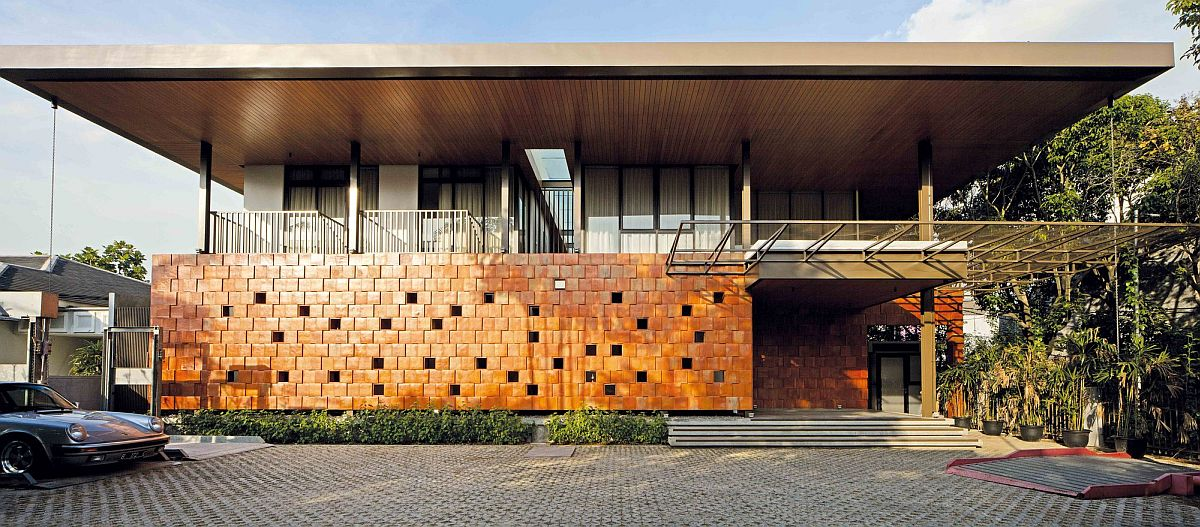 Terracotta street facade of the Jakarta home with holes that let in sunlight