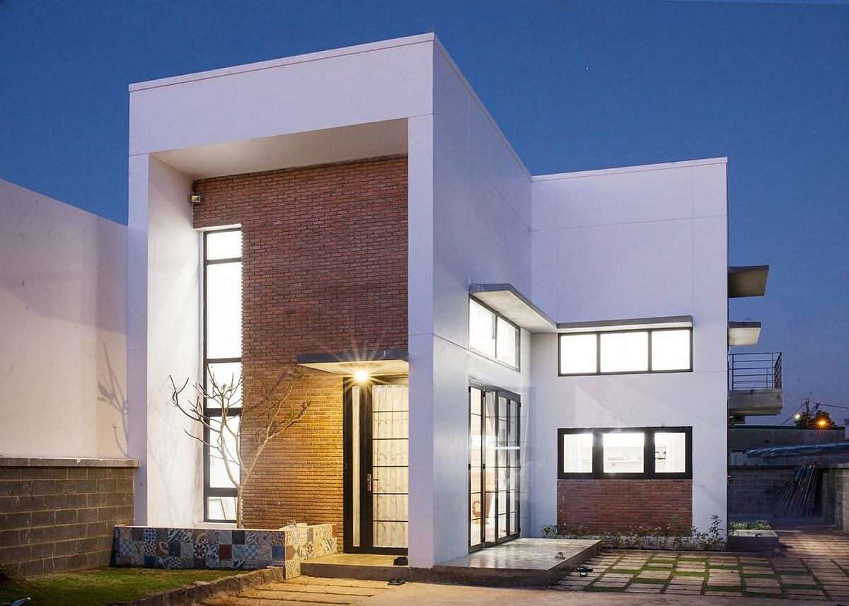 Thick brick wall gives the facade of the house a unique modern industrial look A Quest for Serenity: Family Residence with Brick Walls and Indoor Greenery