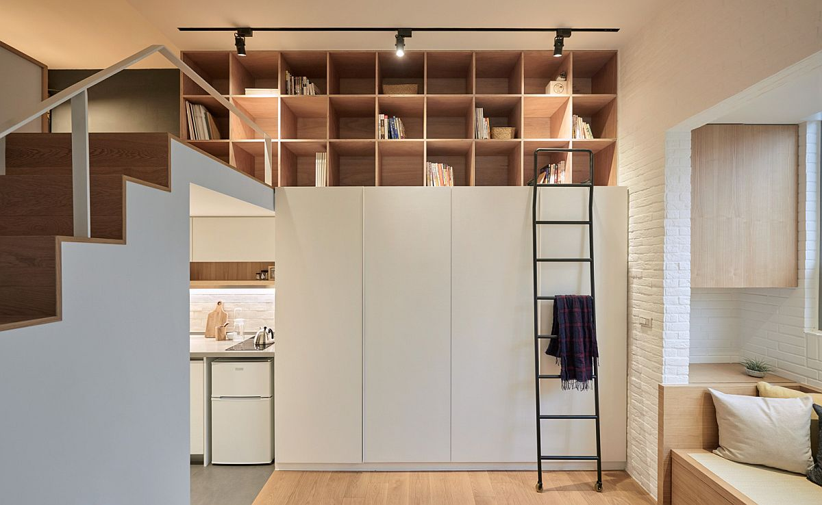 Track lighting illuminates the open shelves above the wardrobe