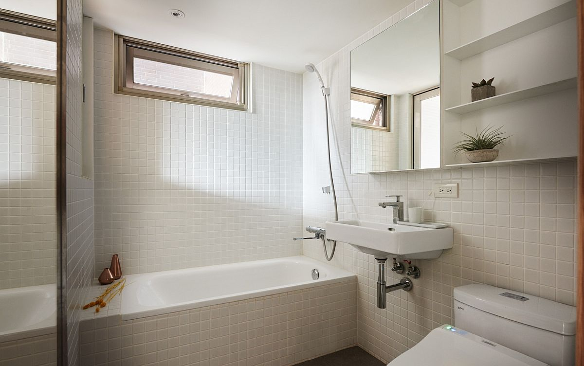 White tiles and natural light give the bathroom a spacious and airy appeal