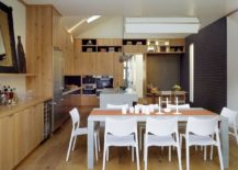 Wooden surfaces give the modern kitchen and dining a mellow, traditional vibe