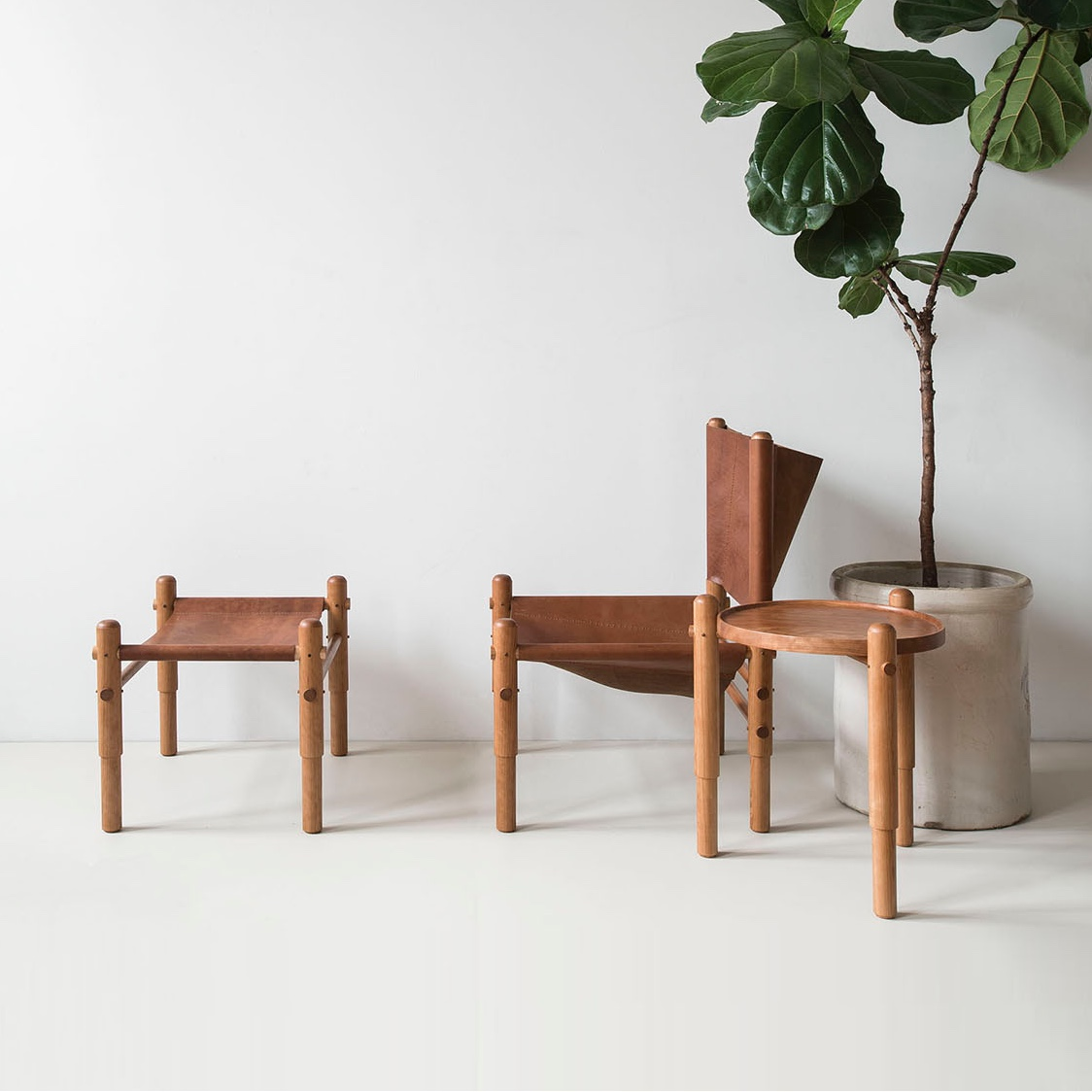 L ro R: Sling Chair, Sling Ottoman and Spool Side Table. Wood and leather. Clean, simple and unique.