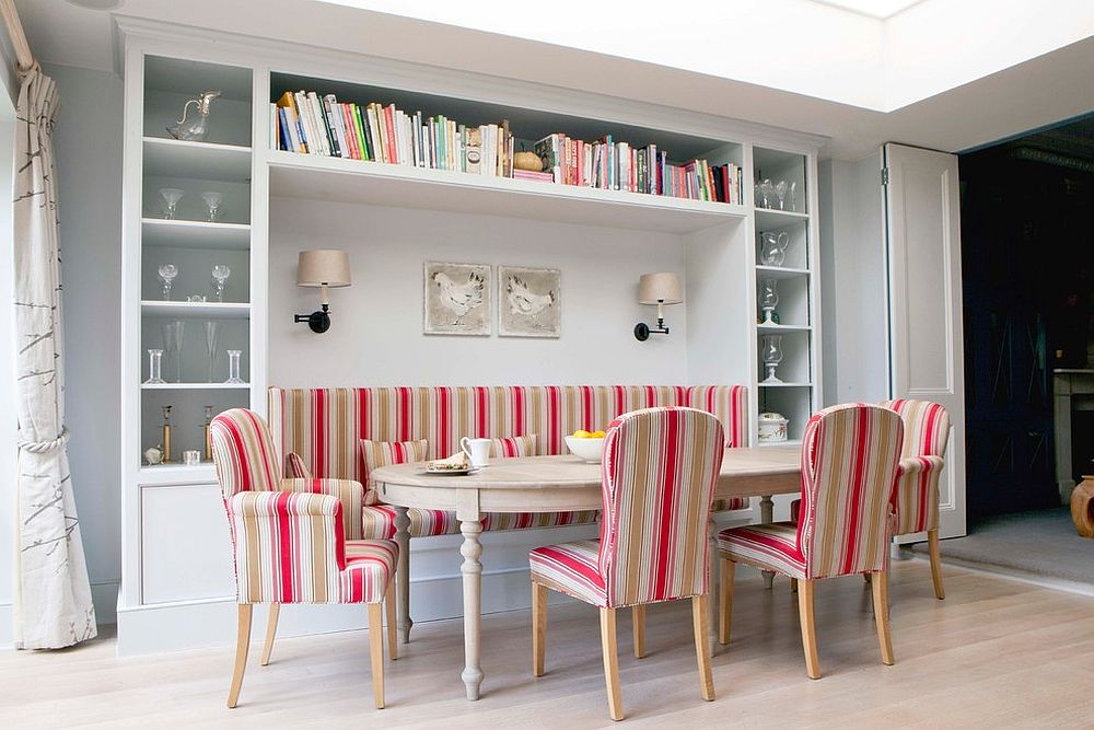 Banquette seating for the Scandinavian dining space with smart shelves all around and colorful chairs [Design: Fiona Andrews Interiors Limited]
