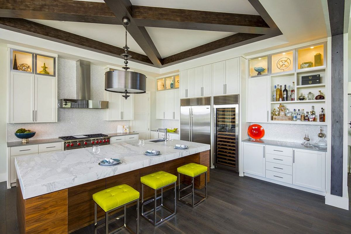 Bar stools bring yellow to the modern kitchen featuring smart marble-top island