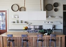 Beach style kitchen with kitchen island draped in reclaimed timber planks