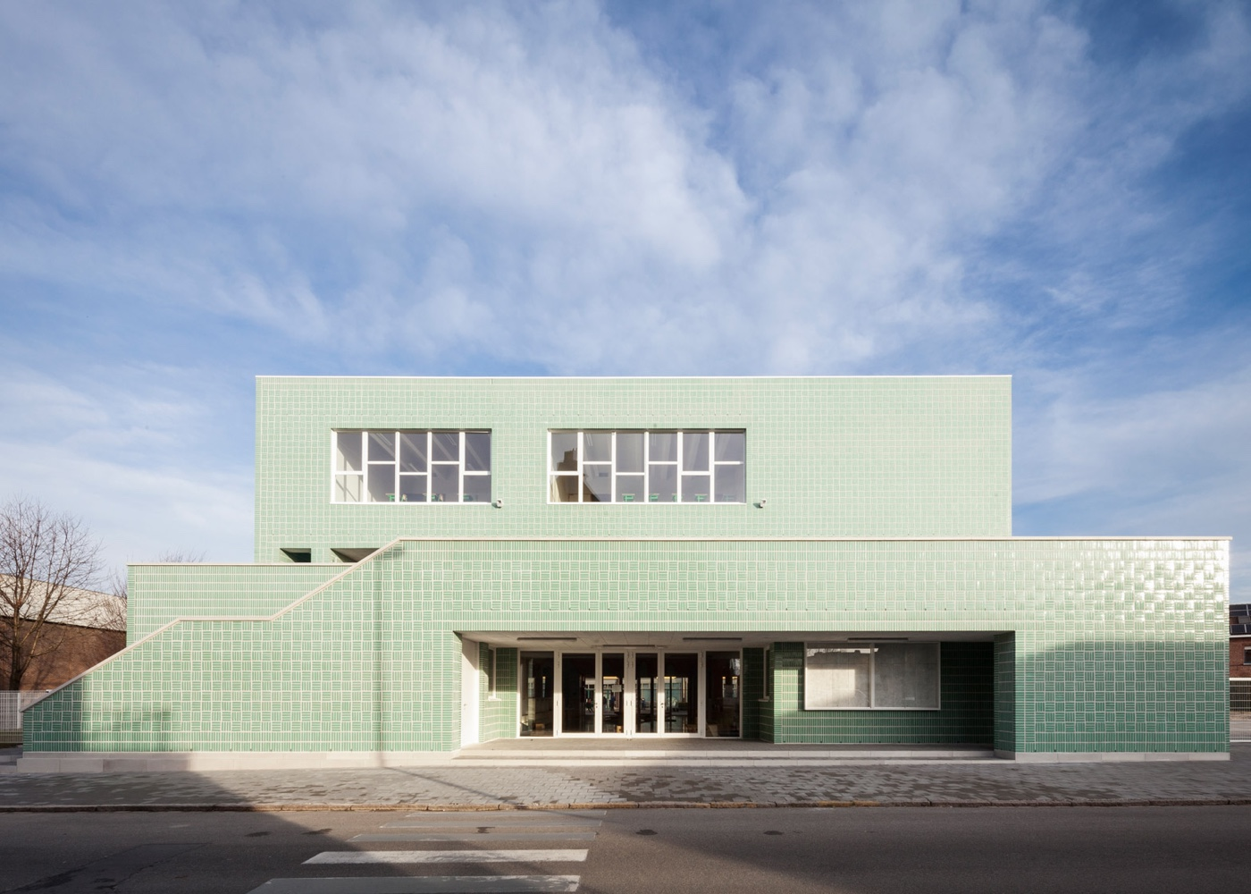 Fresh mint-green glazed bricks adorning a school facade.
