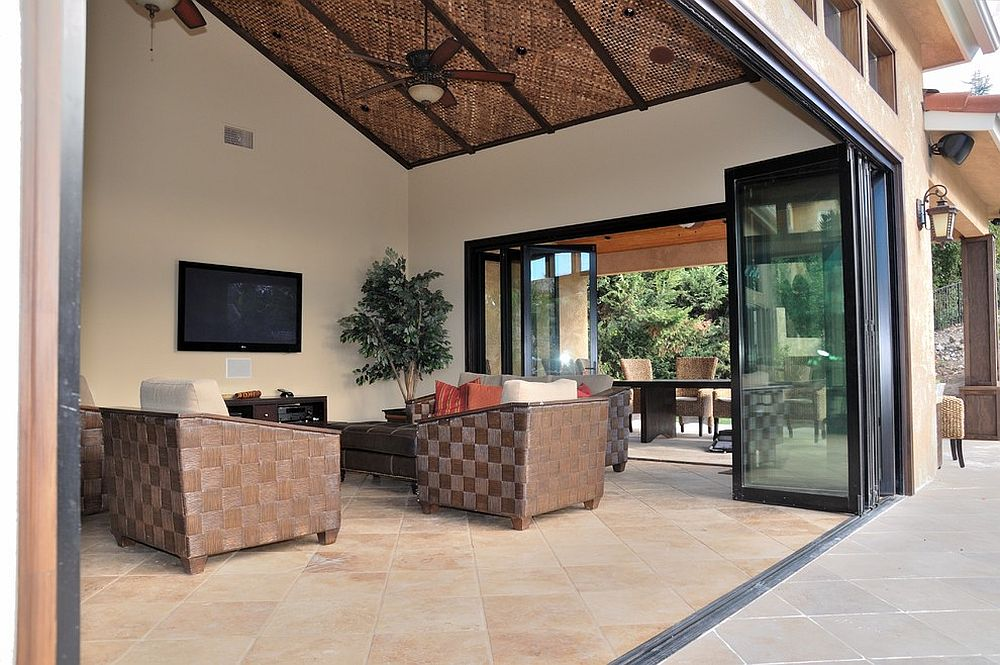 Bifolding stackable doors open up the serene sunroom to the patio outside
