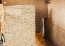 Brick and earthen walls give the double height living space a cool, inviting vibe