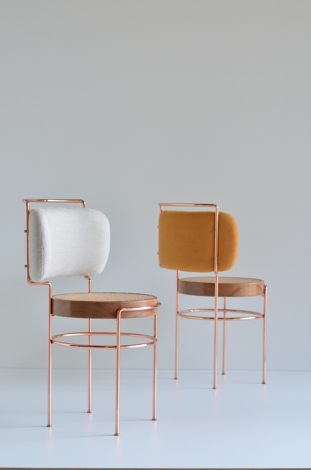 Cadeira IAIÁ by Gustavo Bittencourt draws inspiration from Brazilian modernism. Appearing feminine in shape, the chair is made using copper, solid wood, straw (for the seat) and fabric (for the backrest).