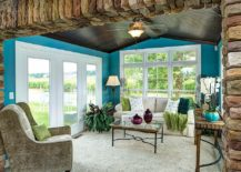 Cheerful tropical sunroom with dark ceiling and walls in bright blue