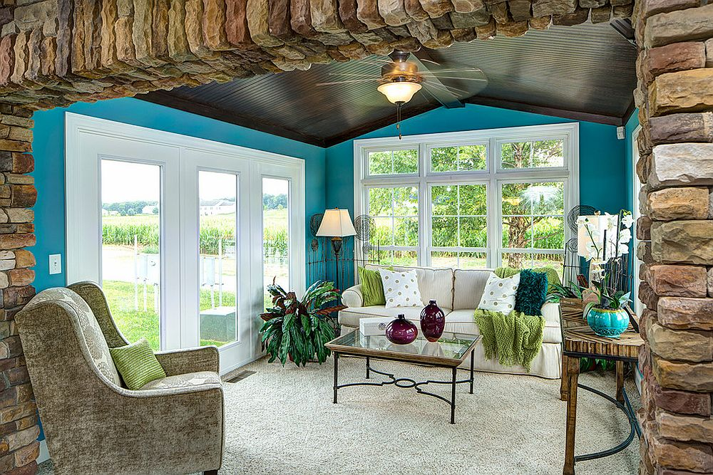 Cheerful tropical sunroom with dark ceiling and walls in bright blue [Design: Schumacher Homes]