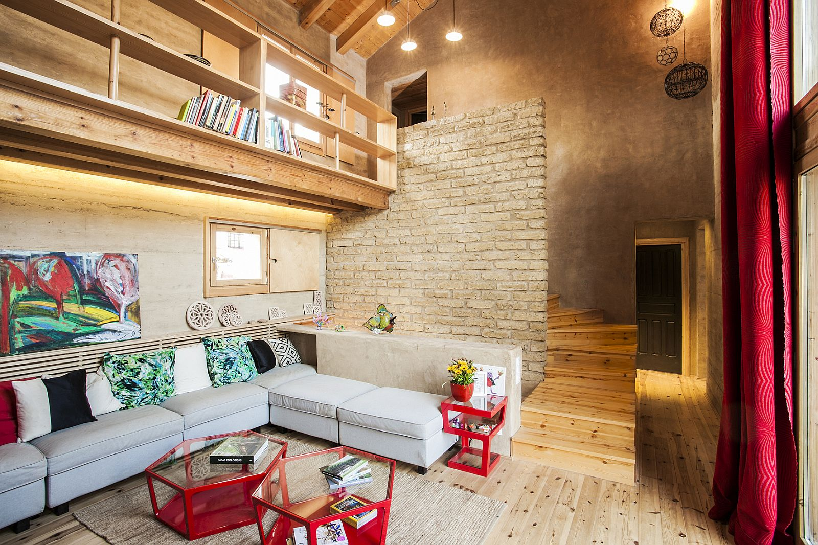 Coffee tables in red and lighting bring brightness to the living area