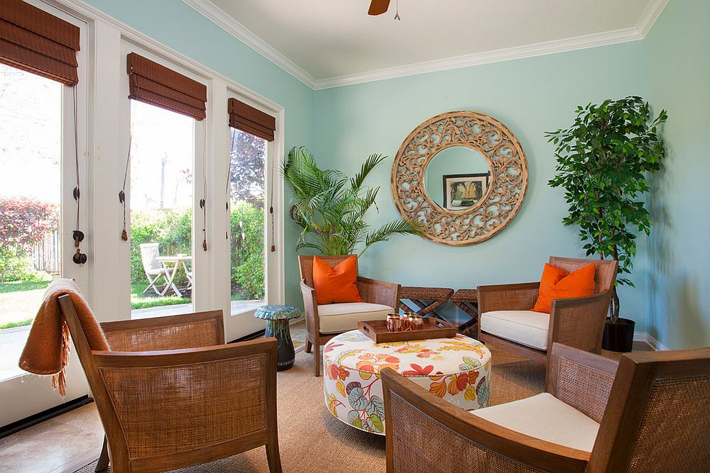 Colorful tropical sunroom with pops of orange and a gentle blue backdrop [From: Deborah Gordon Designs]