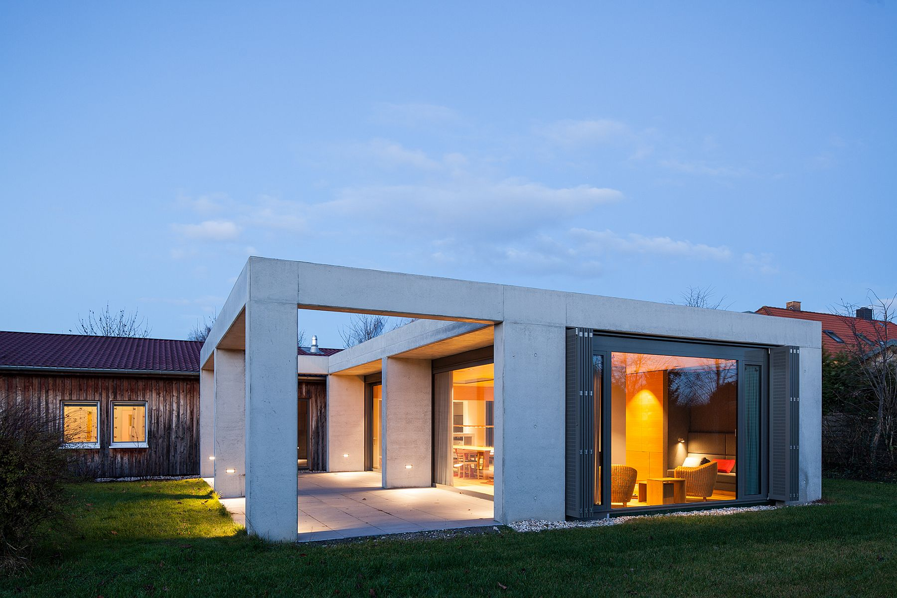 Contemporary concrete extension stands in contrast to the original timber home
