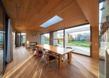DIning room draped in wood with skylight and unabated view of the green scenery outside 217x155 Glass and Concrete Pavilion Extends Timber Paneled Home in Leipzig