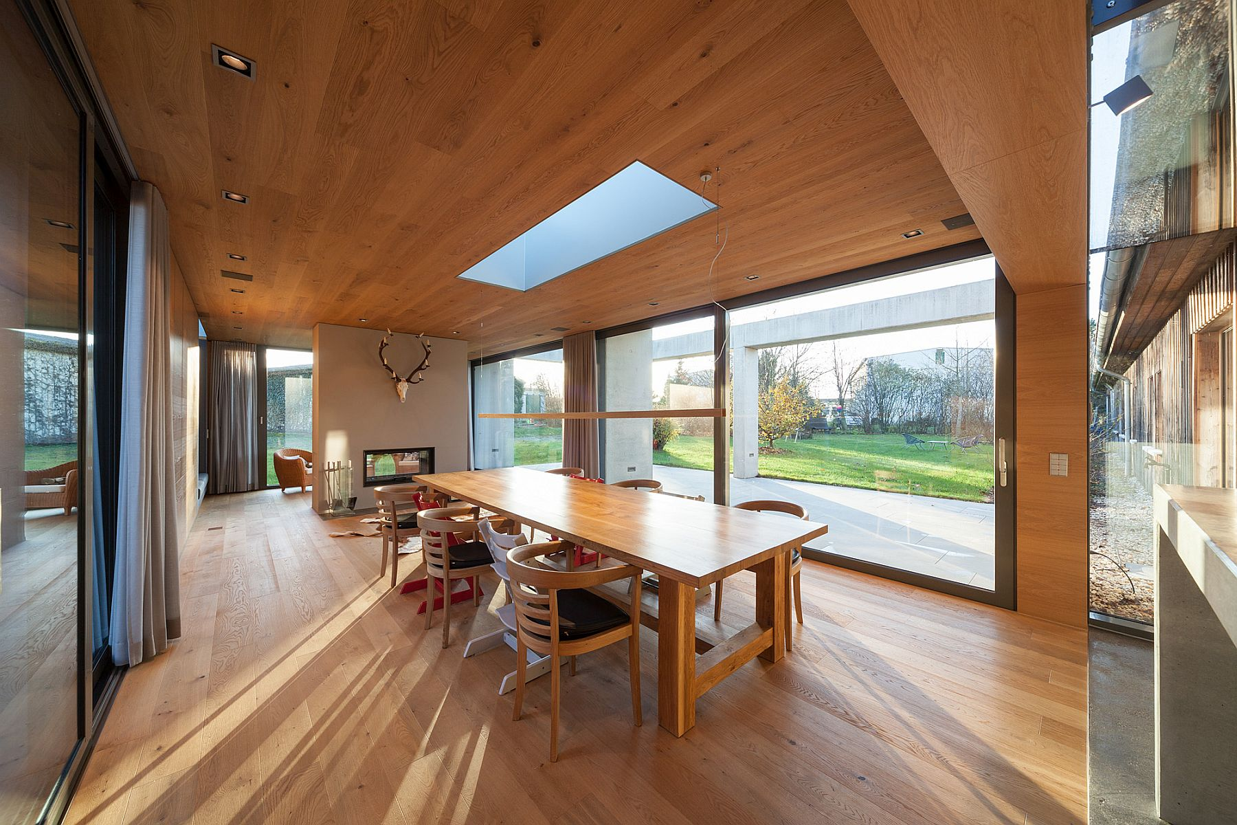 DIning room draped in wood with skylight and unabated view of the green scenery outside
