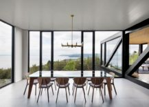 Dining room with cape views and glass walls exudes a sense of minimalism