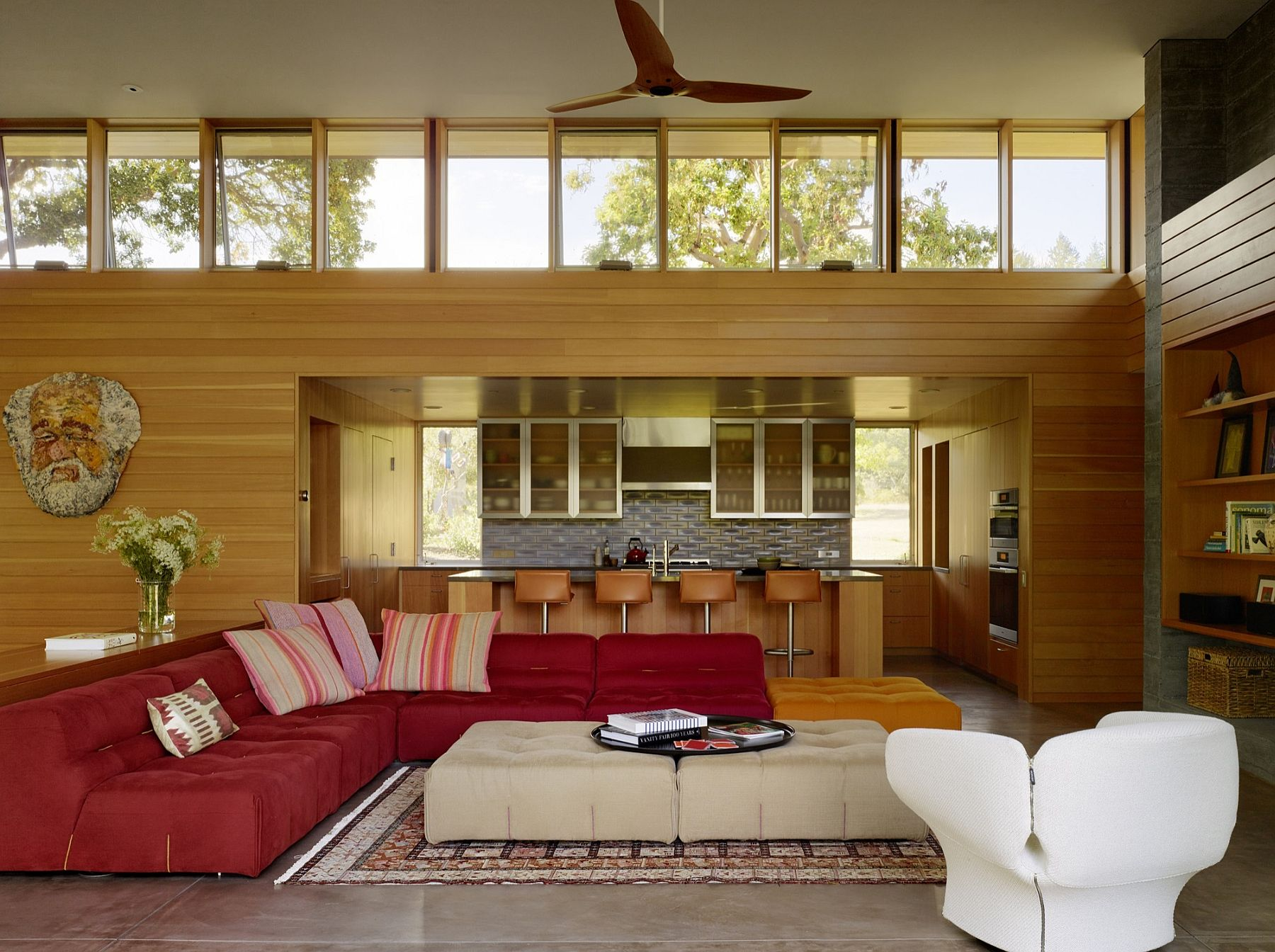 Double height living room with a striking red sectional at its heart