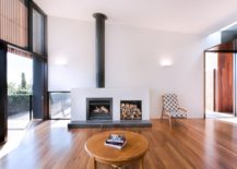 Fireplace with stacked wood next to it in th open living area