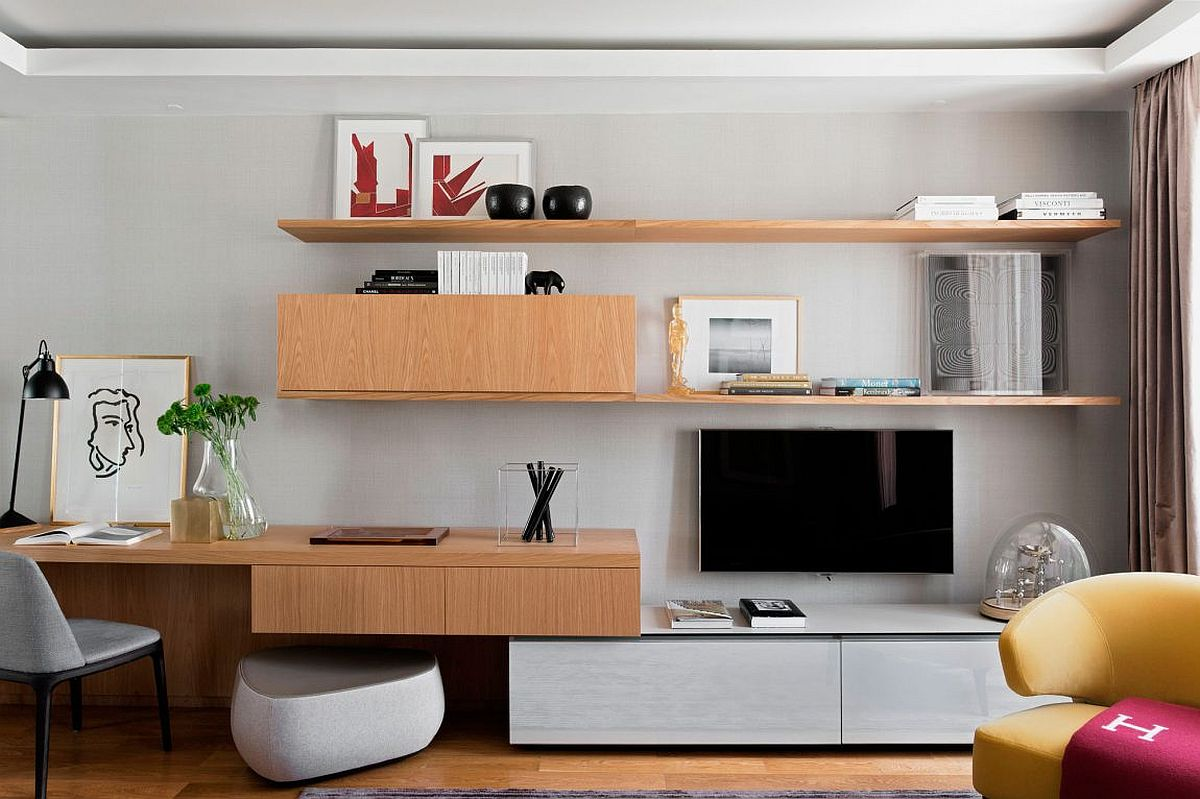 Floating wooden shelves and cabinets make use of corner in the living room