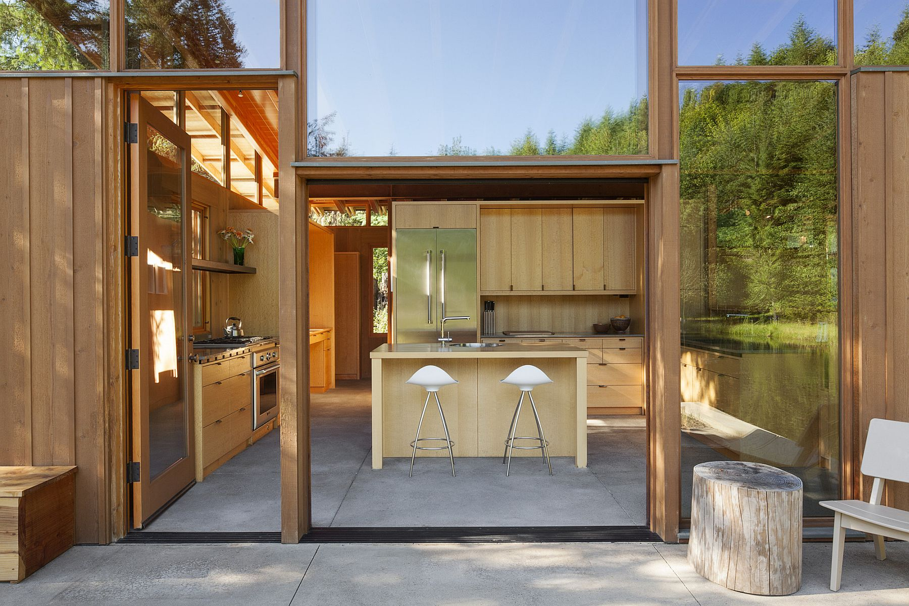 Glass walls of the home reflect the natural canopy around it