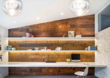 Gorgeously lit shelves and reclaimed wood wall create a stunning midcentury modern home office