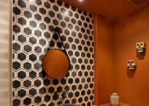 Hexagonal tile pattern brings geometric contrast to the powder room in orange