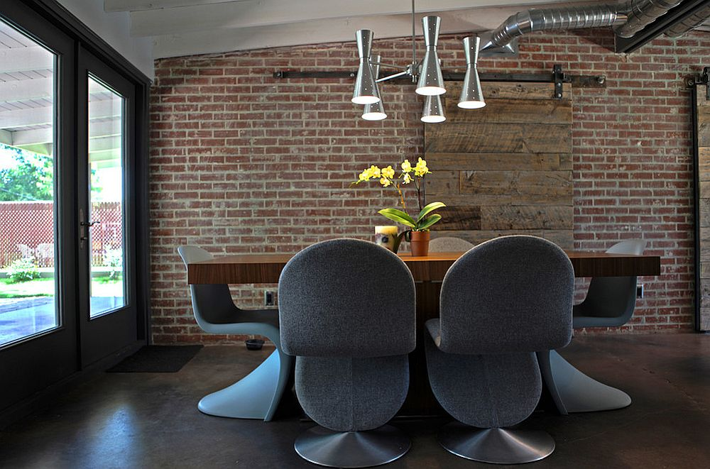 Industrial dining room with brick wall and sliding barn door [Design: The Ranch Mine]
