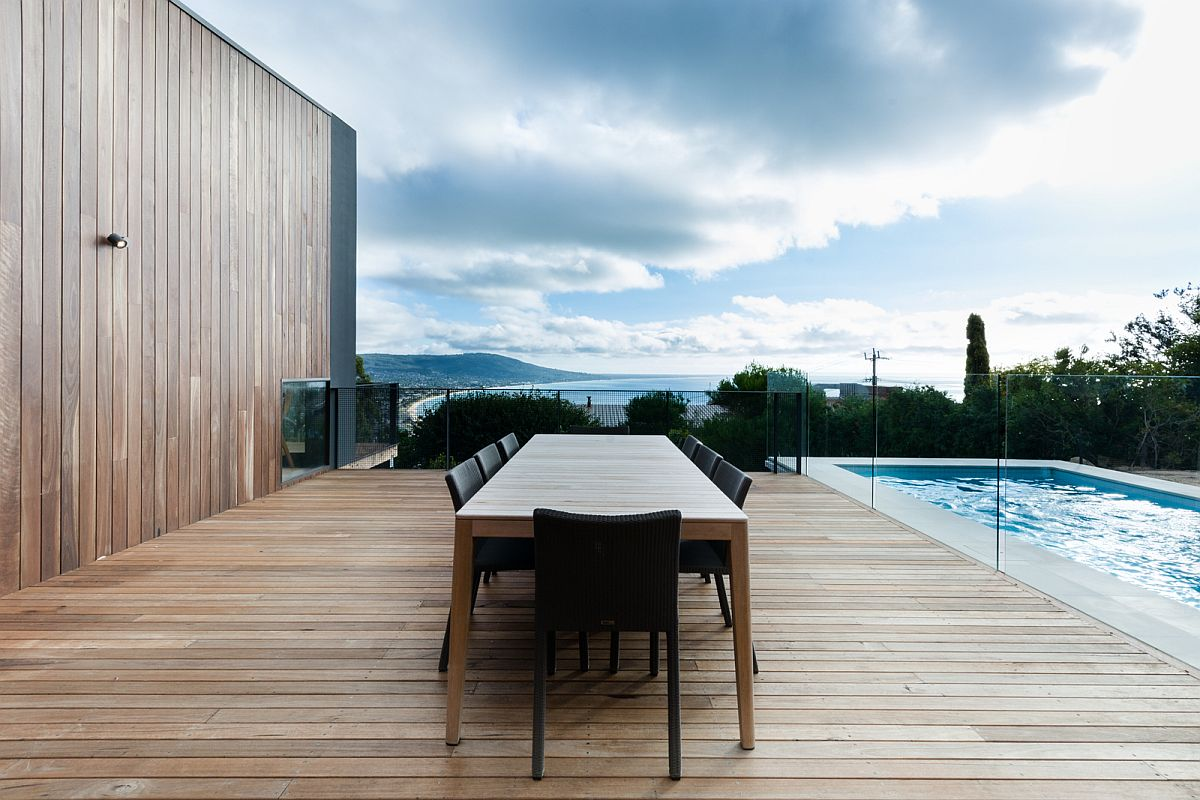 Large woodend deck and pool of the beach residence with a view of the coastline