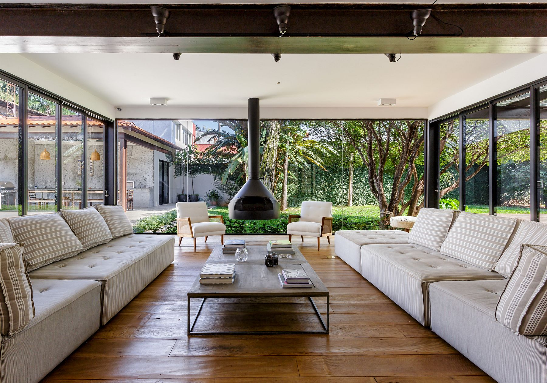 Living room with glass walls and fireplace connecetd with the garden and the pool outside