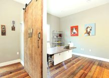 Modern home office with reclaimed wood flooring and a cool sliding barn door