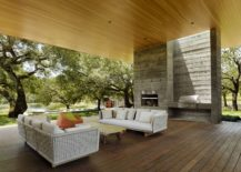 Open, outdoor living areas with shade overlook the natural pond and the greenery beyond