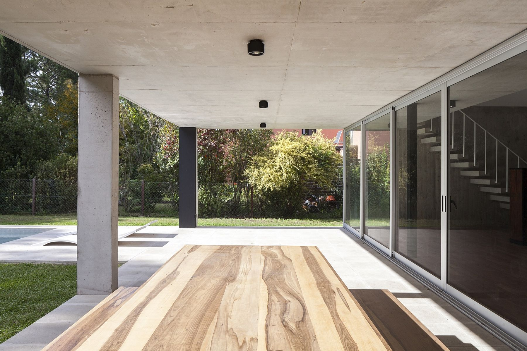 Outdoor dining space under the natural structure of the home that acts as the pergola