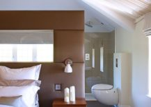Plush headboard acts as a divider between the bedroom and the master bath
