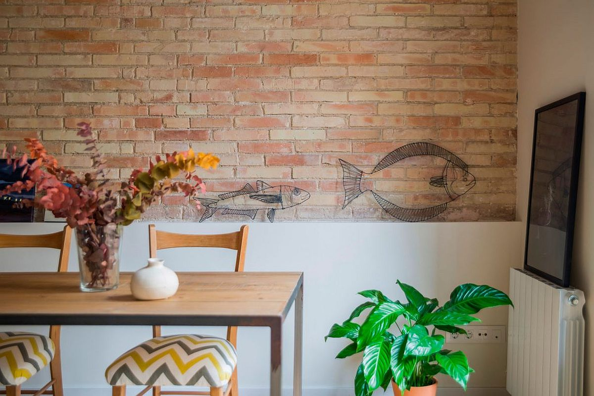 Restored and exposed brick walls add artistic value to the renovated home in Eixample District