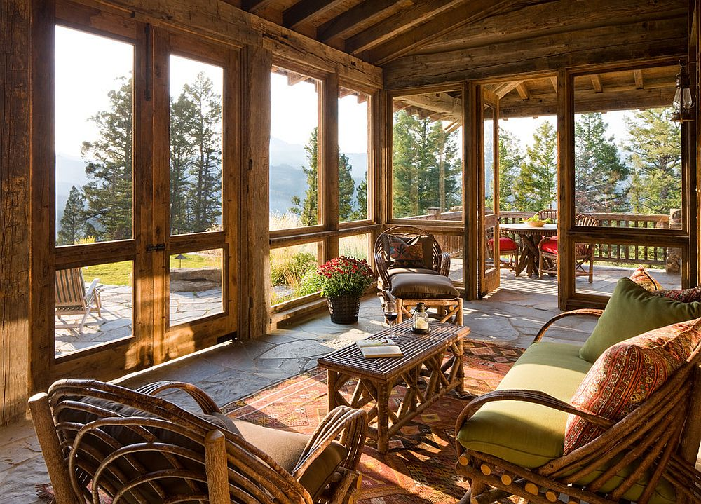 Rustic sunroom that flows into the deck acts as a bridge between the interior and the outdoors