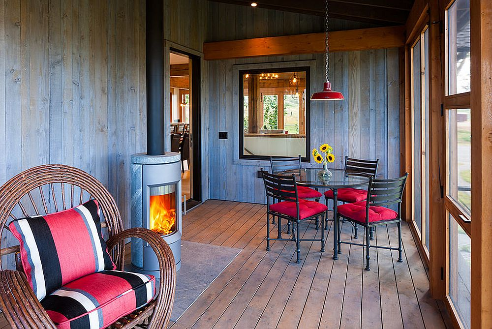 Screened porch sunroom with fireplace and colorful décor [Design: Dovetail Construction]