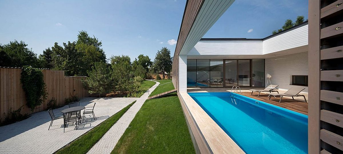 Semi-open deck of a terrace with a swimming pool, play area and graden outside at the Ark
