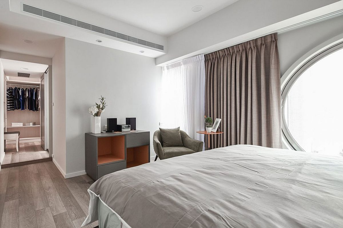 Sheer curtains coupled with gray drapes in the bedroom