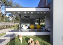 Sitting area with glass walls extends outside from the central living zone