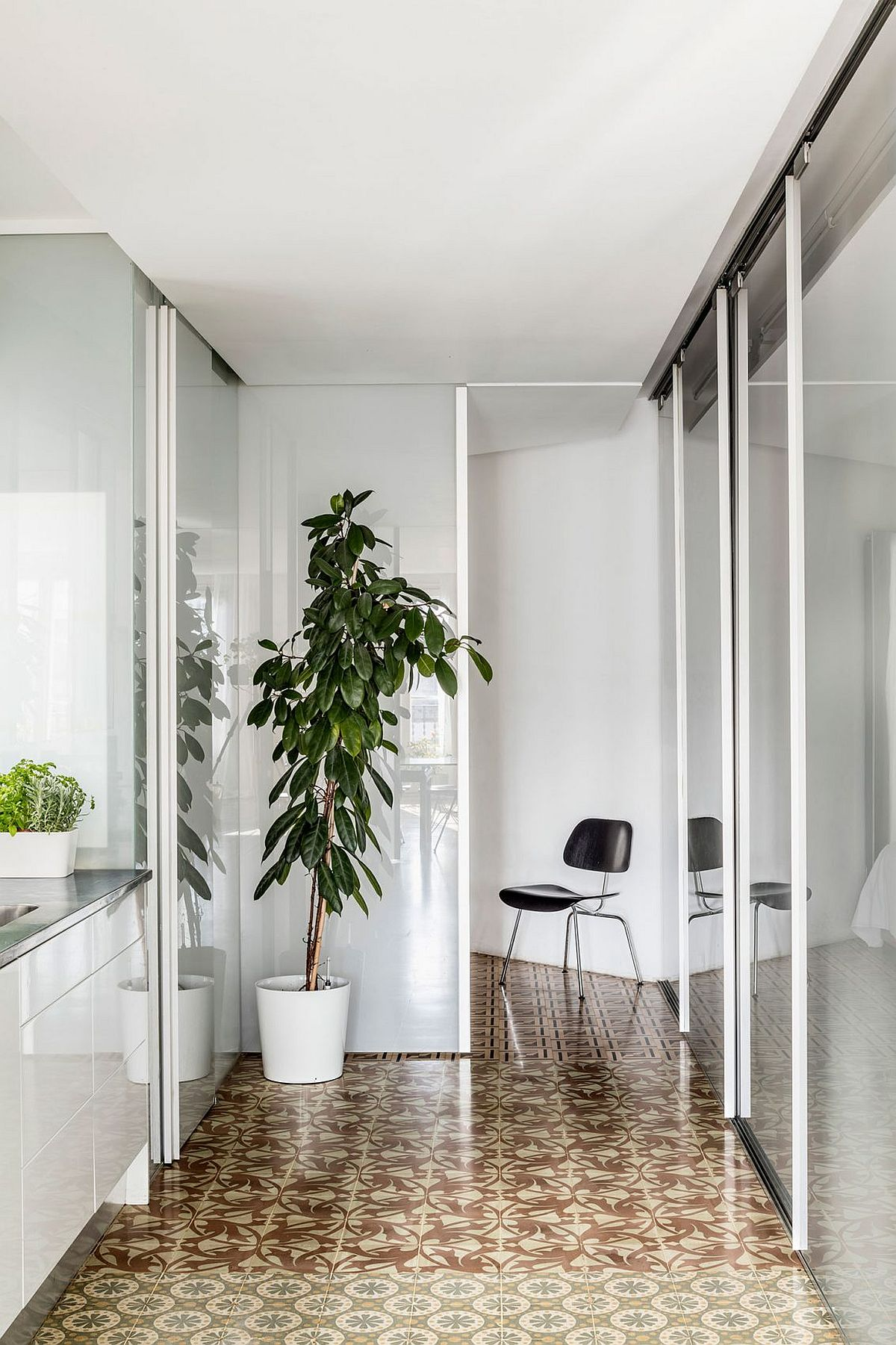 Sliding glass doors and partitions coupled with mosaic flooring inside the renovated Barcelona home