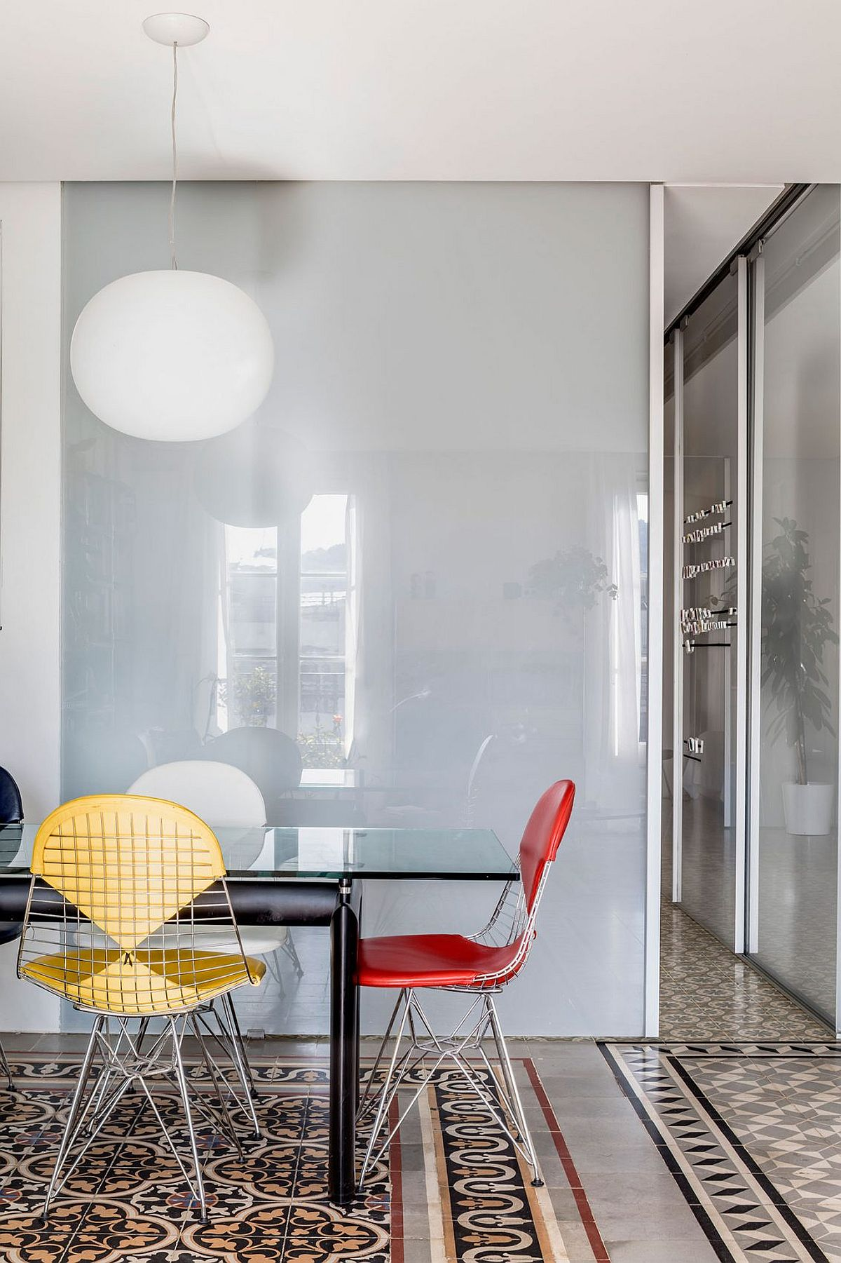 Small dining area with colorful chairs and glass top dining table
